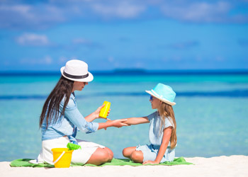 Mother applying sunscreen to her daughter on the beach