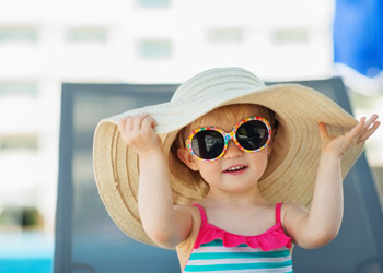 Little girl wearing a wide-brim hat and sunglasses